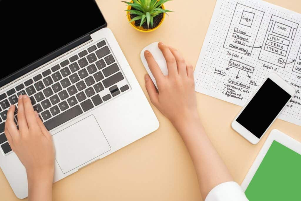 partial view of designer using laptop near gadgets, website design template and green plant on beige